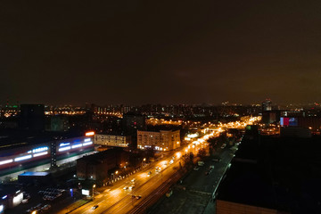 Aerial view of the night city. A wide motor road runs through the city block
