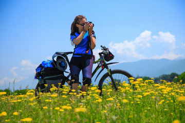 A girl with a bicycle shoots a photo on a flowered field