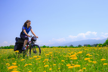 Girl tourist rides a bike among the flowering fields on the background of high mountains