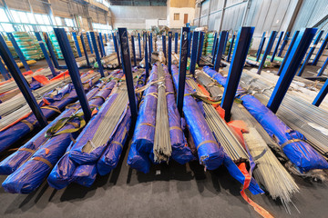 Large industrial warehouse of cold-rolled metal bar. Bundles of metal rods are stacked