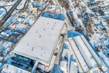 Large warehouse hangar, industrial zone of the city. Sunny winter day.