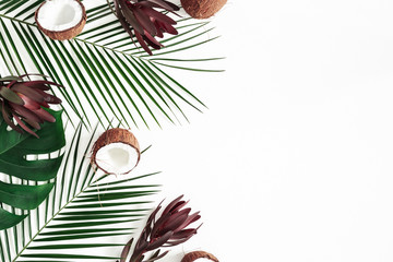 Summer composition. Tropical palm leaves, flowers, coconut on white background. Summer concept. Flat lay, top view, copy space