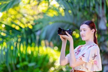 Young Woman Photographer Taking Photos In A Garden