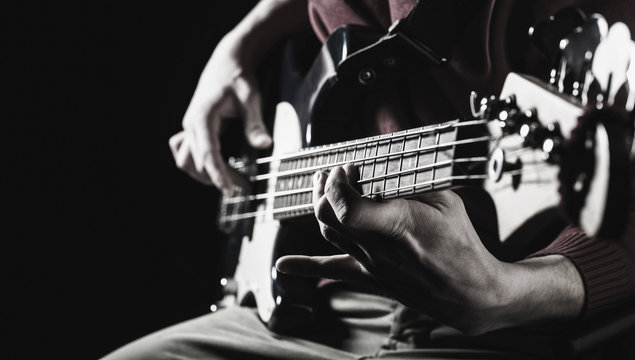 Music concept. Electric guitar. Copy space. Play the guitar. Live music background. Music festival. Instrument on stage and band. Black and white.