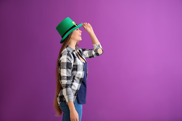 Beautiful young woman in green hat on color background. St. Patrick's Day celebration