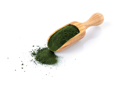 chlorella and spirulina powder in a wooden scoop isolated on white