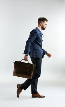Fashionable young man in formal clothes and with bag walking against light background