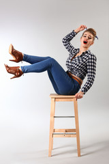 Beautiful pin-up woman sitting on stool against grey background