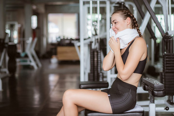 Young attractive using towel to wipe the sweat. Relaxation after hard workout in gym.