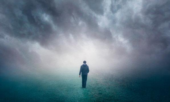 Man walking alone on misty foggy countryside field.
