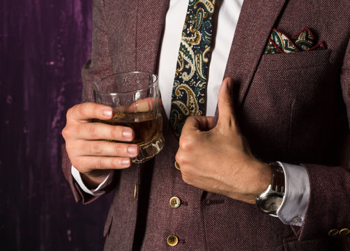 business man with whiskey in his hand shows a hand sign that everything is in order