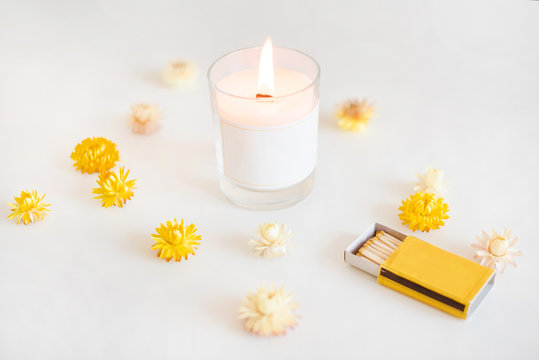 Wooden wick candle with matches and yellow flowers. Elegant home decoration. Burning wax scented candle.