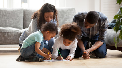 Black family with little kids painting together in living room