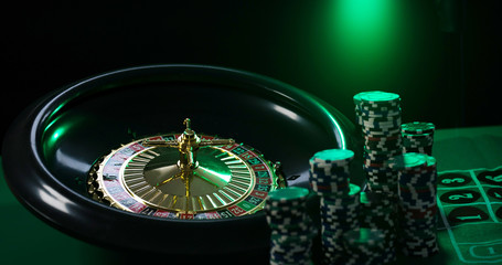 Casino background,  poker Chips on gaming table, roulette wheel in motion,
