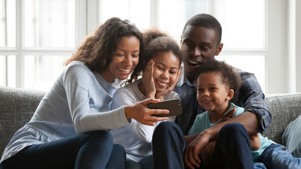 Smiling black family relax together watching cartoons on smartphone