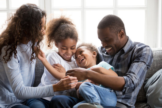 Smiling black family have fun at home with little kids