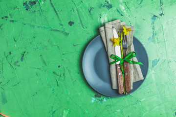 Empty blue plate and cutlery with daffodils on a napkin
