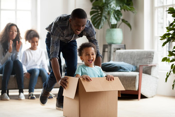 Happy black family play with kids moving to new home