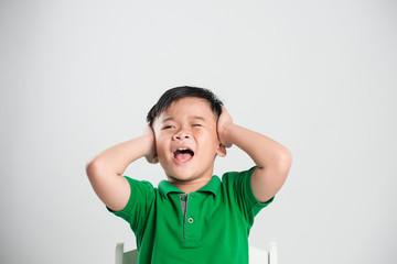 Young boy and closed eyes covering ears with hands