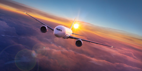 Poster Airplane Commercial airplane jetliner flying above dramatic clouds in beautiful sunset light. Travel concept.