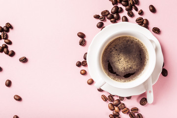 White cup of coffee with coffee beans on pink background.