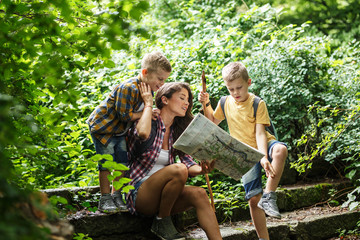 Mother and her little sons hiking .They taking a break and sitting on the old stairs.Examining map.