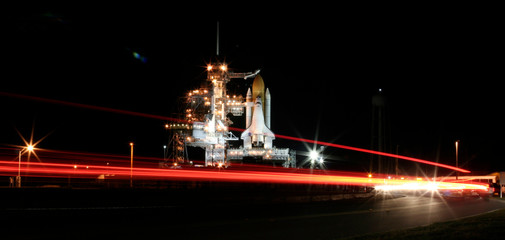 The space shuttle Atlantis stands poised on the launch pad as workers prepare it for launch in Cape Canaveral