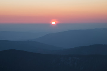 sunrise in the Carpathians on the background of blue mountain ranges and solar disk on the horizon.