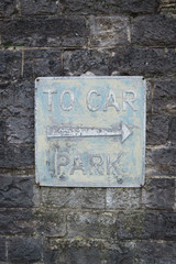 Old car park sign on stone wall