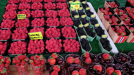 Forest fruit such as blueberries, raspberries, strawberries, and cherries in disposable plastic containers and paper baskets at the Farmers Market, convenient snack or healthy choice dessert on the go