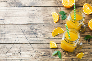 Orange juice in glass jars and fresh oranges on a wooden rustic background. Copy space.
