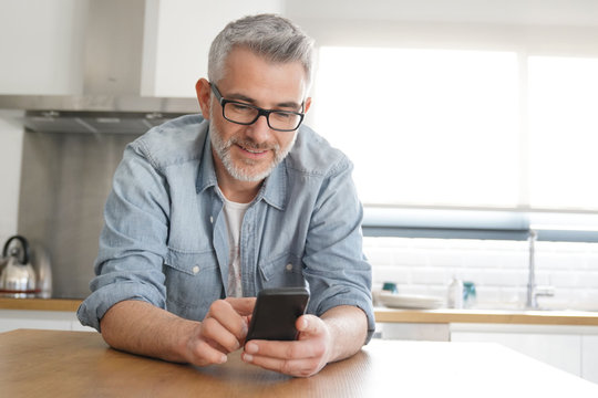 Man texting casually in kitchen at home