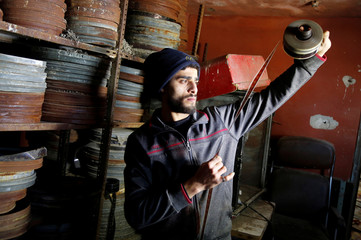 Palestinian worker checks a film roll in a former cinema, in Tulkarm in the Israeli-occupied West Bank