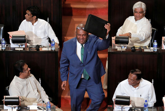 Sri Lankan Finance Minister Mangala Samaraweera shows a briefcase containg the 2019 budget proposals as he arrives at parliament in Colombo