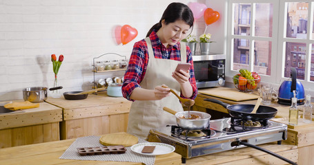 elegant girl stirring melted chocolate in liquid on stove hot water pot. young woman holding spoon and cellphone taking photo recording down process video of making dessert. handmade valentine gift