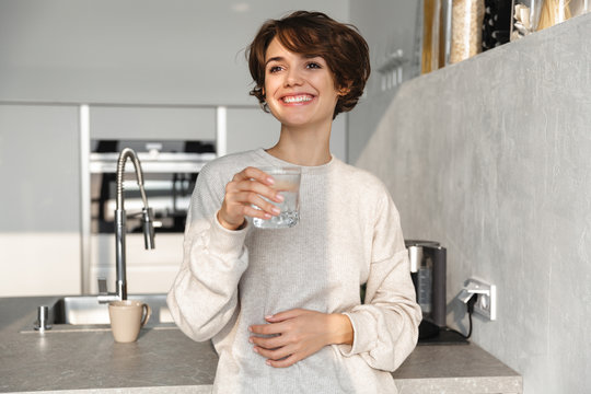Smiling young woman holding glass of water