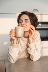 Smiling young woman having cup of tea