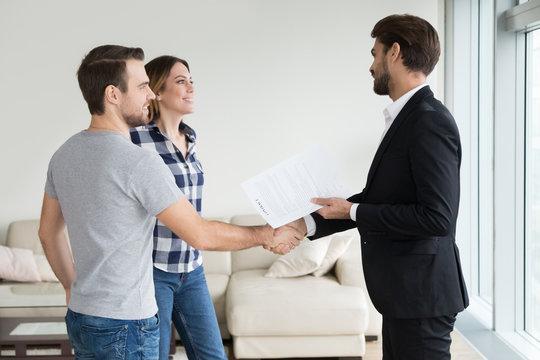 Realtor or landlord handshaking couple tenants make real estate deal