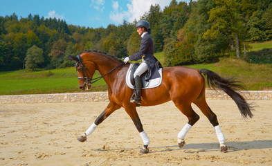 Caucasian girl in a dark blue frock trotting on her beautiful chestnut mare.