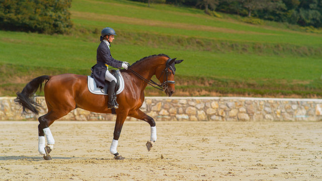 English rider on horseback riding trot around the sandy arena in the countryside