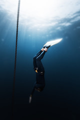 Wall Mural - Freediver in monofin descends into depth along the anchor chain in the sea. Version of the photo with the tilt shift effect applied