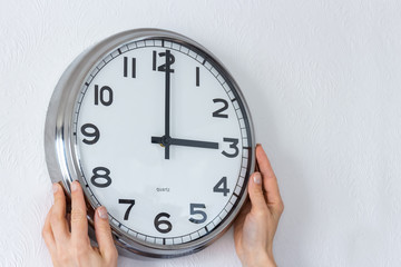Woman hangs a big silver clock on the white wall