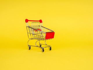 empty shopping cart on yellow background, copy space