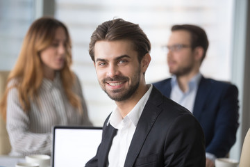 Smiling businessman in suit looking at camera posing at meeting