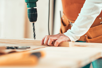 Female carpenter using electric drill