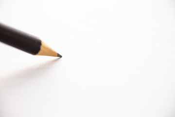 Hand writing letter on white paper background, A black pencil, Close up & Macro shot, Selective focus, Stationery concept