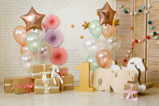 Birthday gold and silver decorations with gifts, toys, garlands and figure for little baby party on a white bricks background.