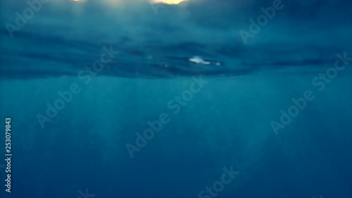 Wall mural Underwater view of a calm tropical sea with waves and ripples during sunset