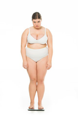 sad young overweight woman standing on scales isolated on white, lose weight concept