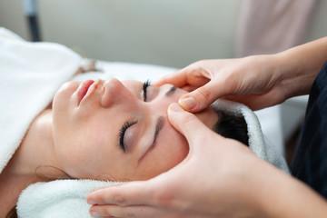 Closeup face of young woman having facial massage at spa.